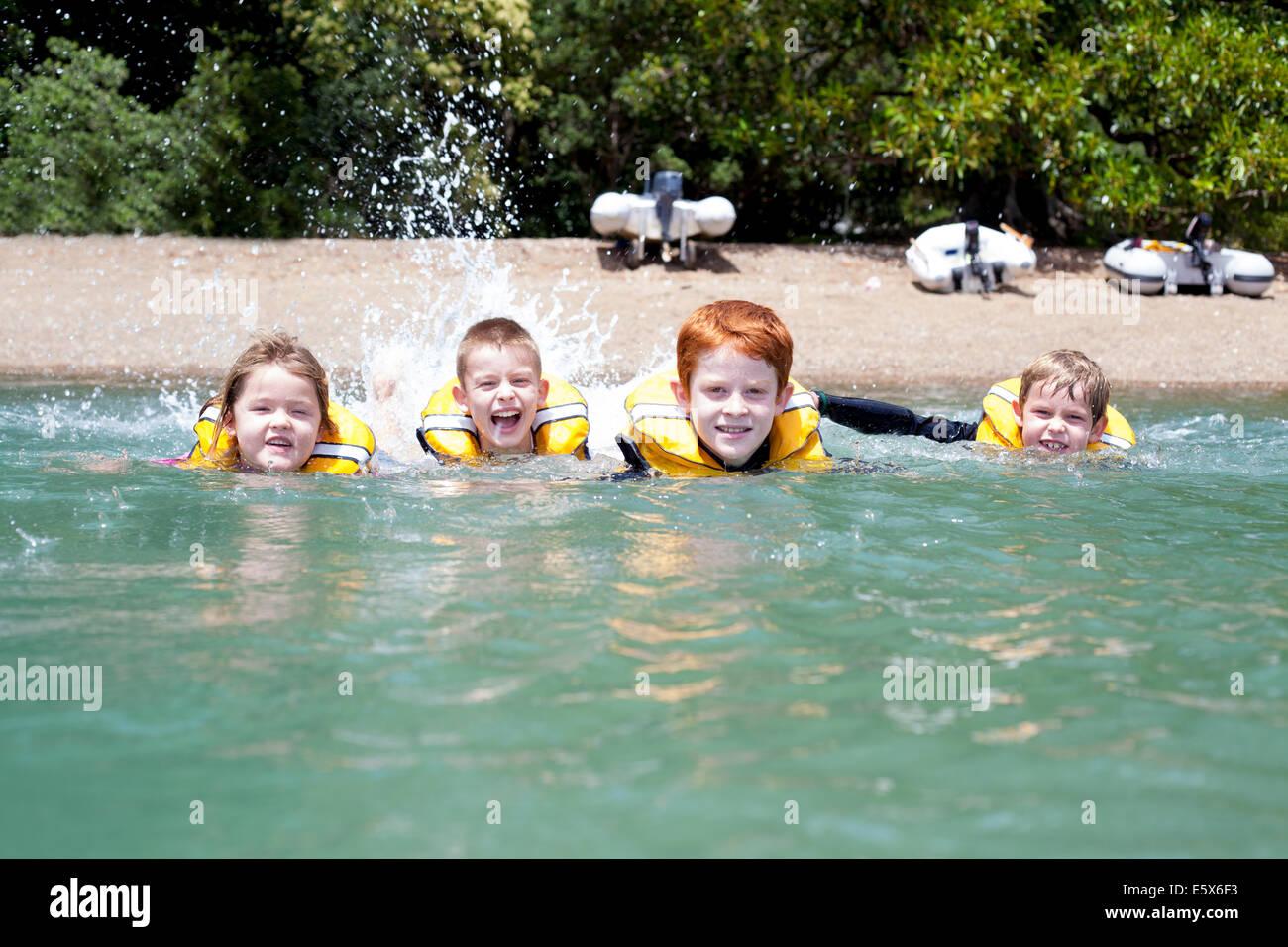 Hermanos y hermanas en una fila de nadar en el mar Imagen De Stock