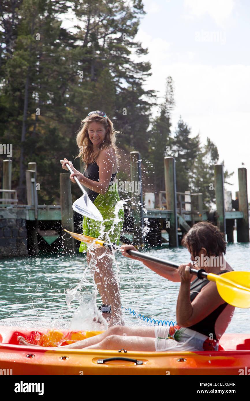 Mujer mayor y su hija salpicaduras mutuamente desde kayak y paddleboard Imagen De Stock