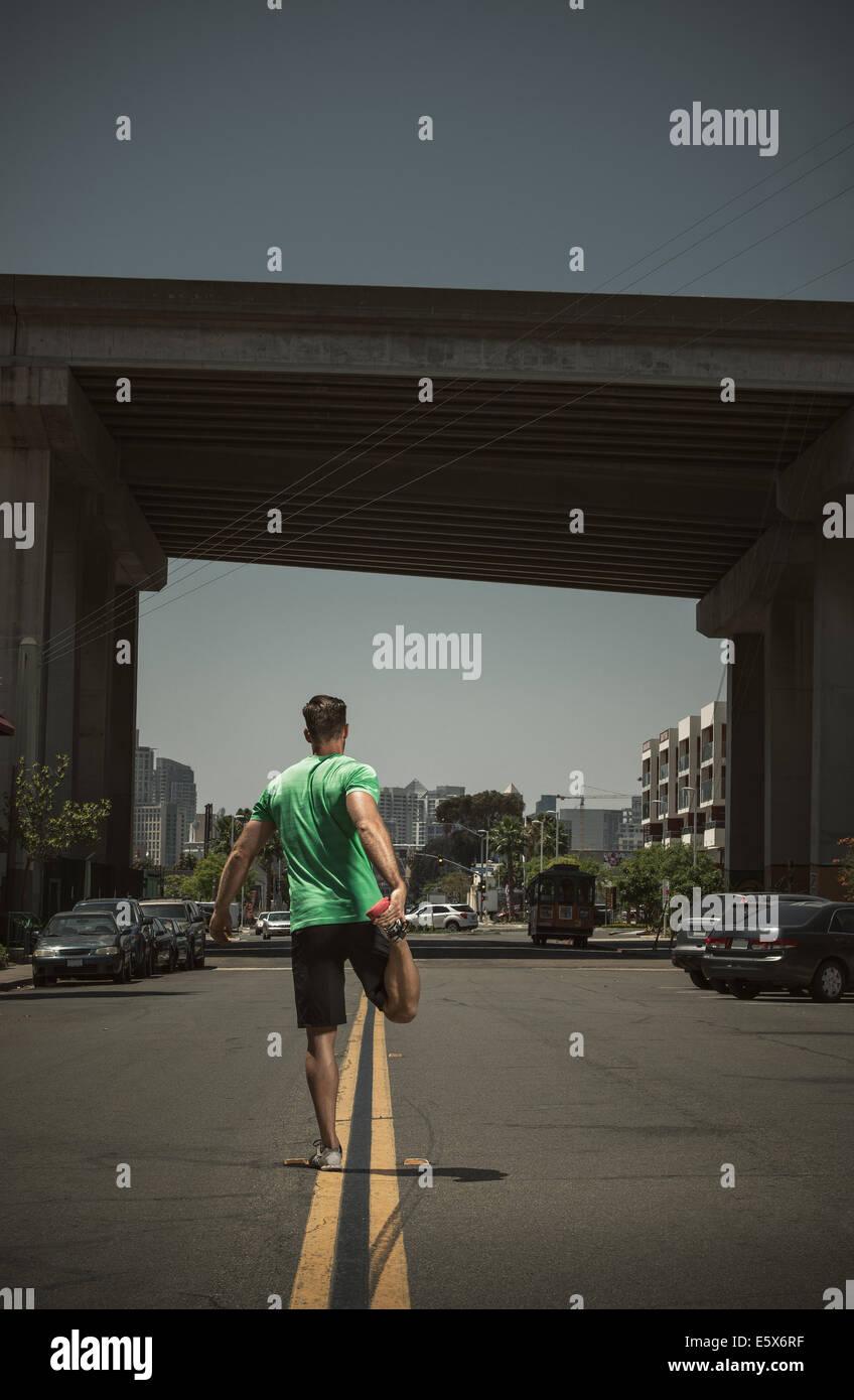 Hombre adulto joven estiramiento en carretera, vista trasera Imagen De Stock