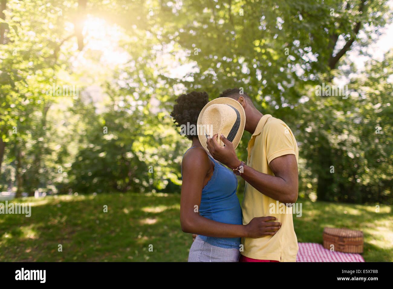 Pareja joven en el parque mantiene sombrero para cubrir caras Imagen De Stock