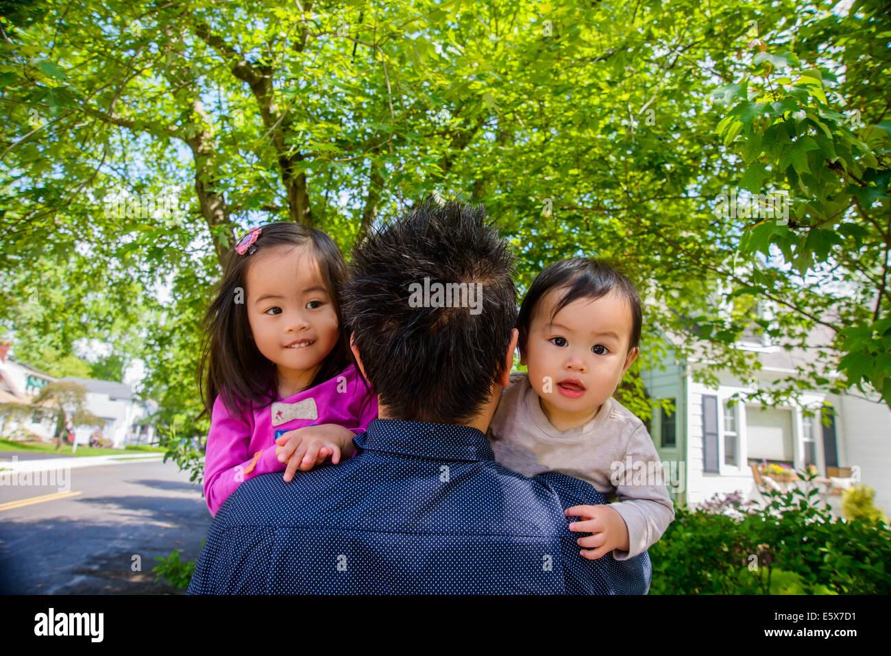 Retrato de mediados adulto padre con Baby Boy y Girl toddler sobre el hombro Foto de stock