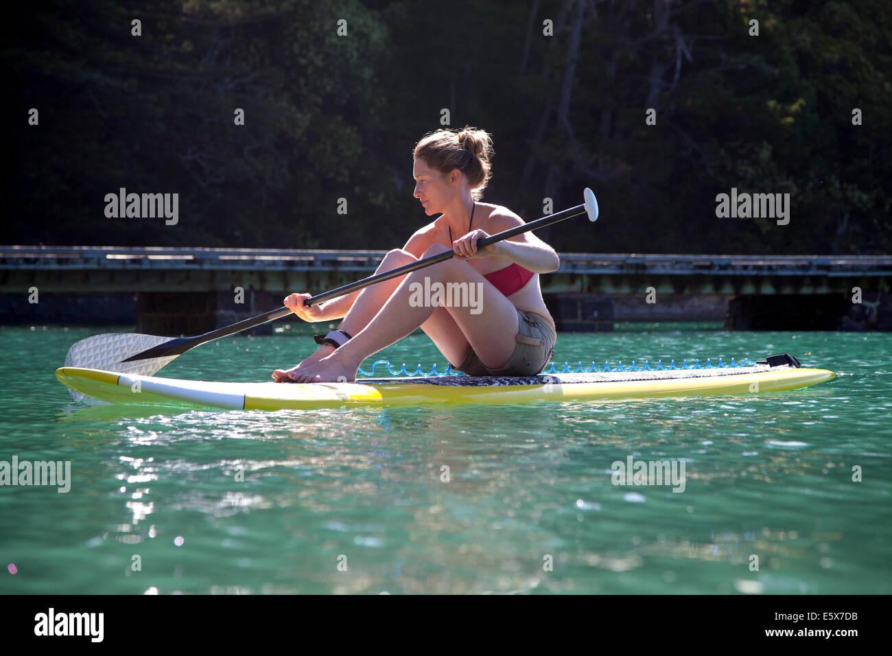 Mujer adulta media sentarse paddleboarding en el mar Imagen De Stock