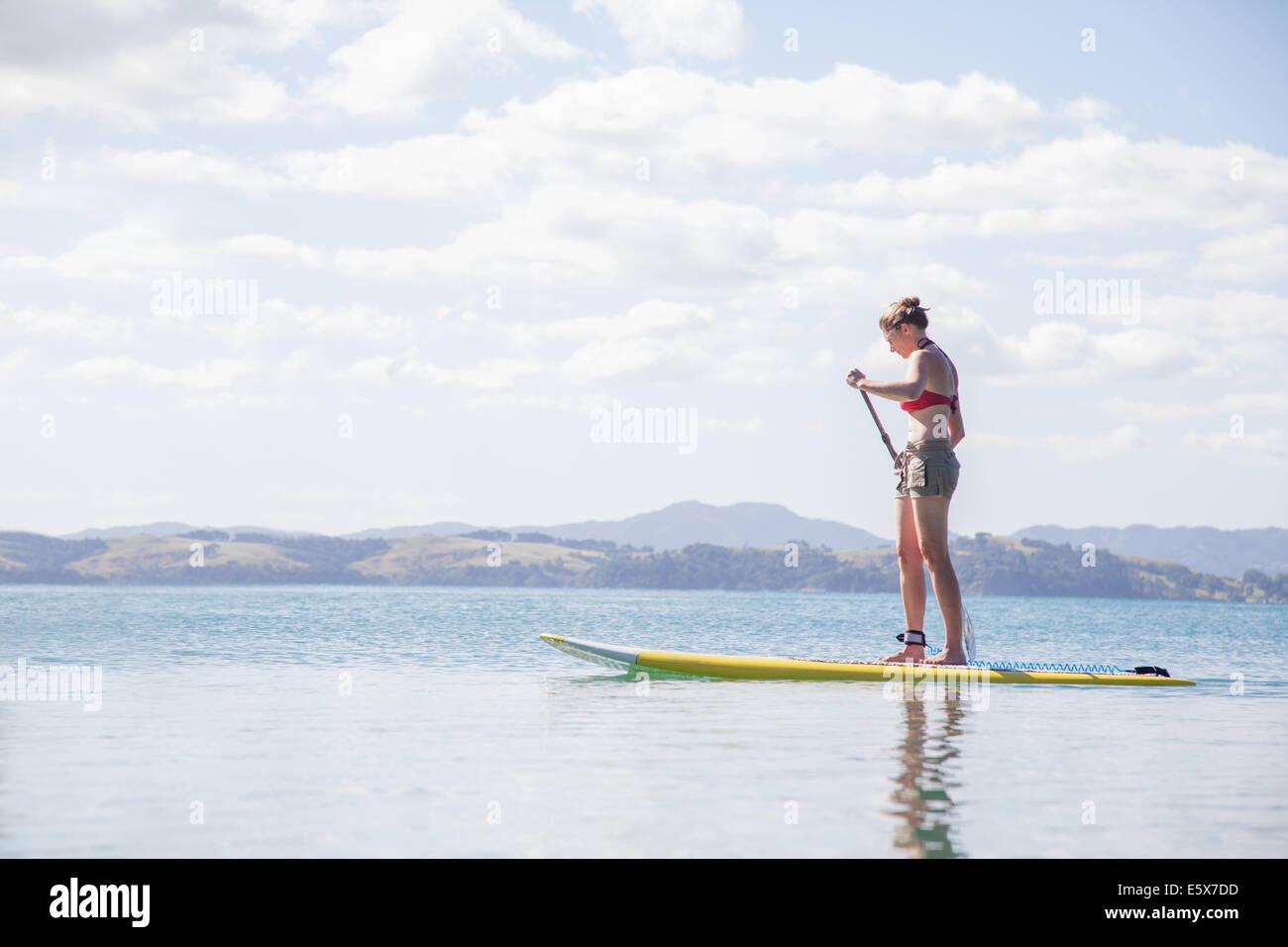 Mujer adulta media levántate paddleboarding en el mar Imagen De Stock