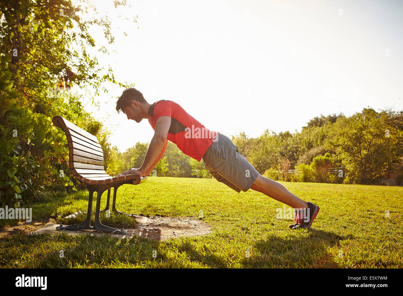 Macho joven corredor haciendo flexiones sobre un banco del parque Imagen De Stock