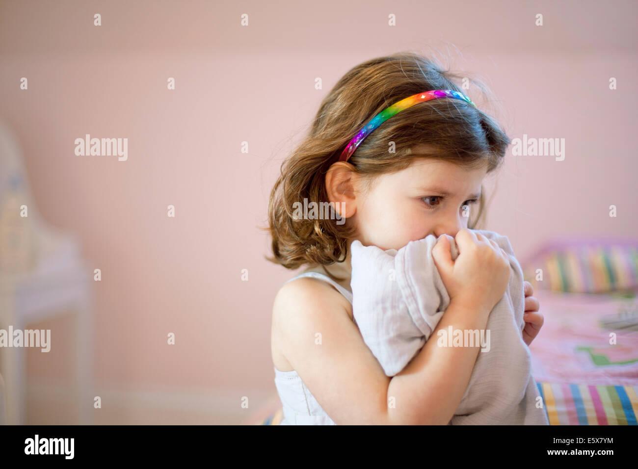 Infeliz niña de tres años en el dormitorio mantiene cómodo manto a cara Foto de stock
