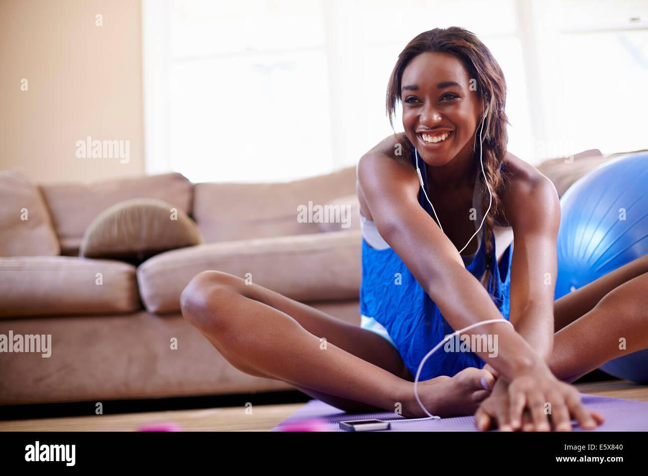Mujer joven ejercicio y estiramiento en el suelo de la sala de estar Imagen De Stock