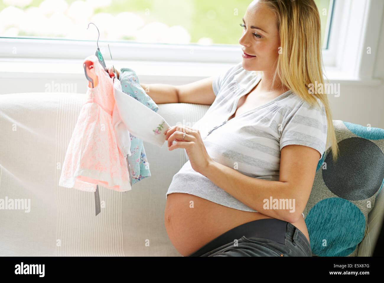 Mujer embarazada mirando ropa de bebé Imagen De Stock