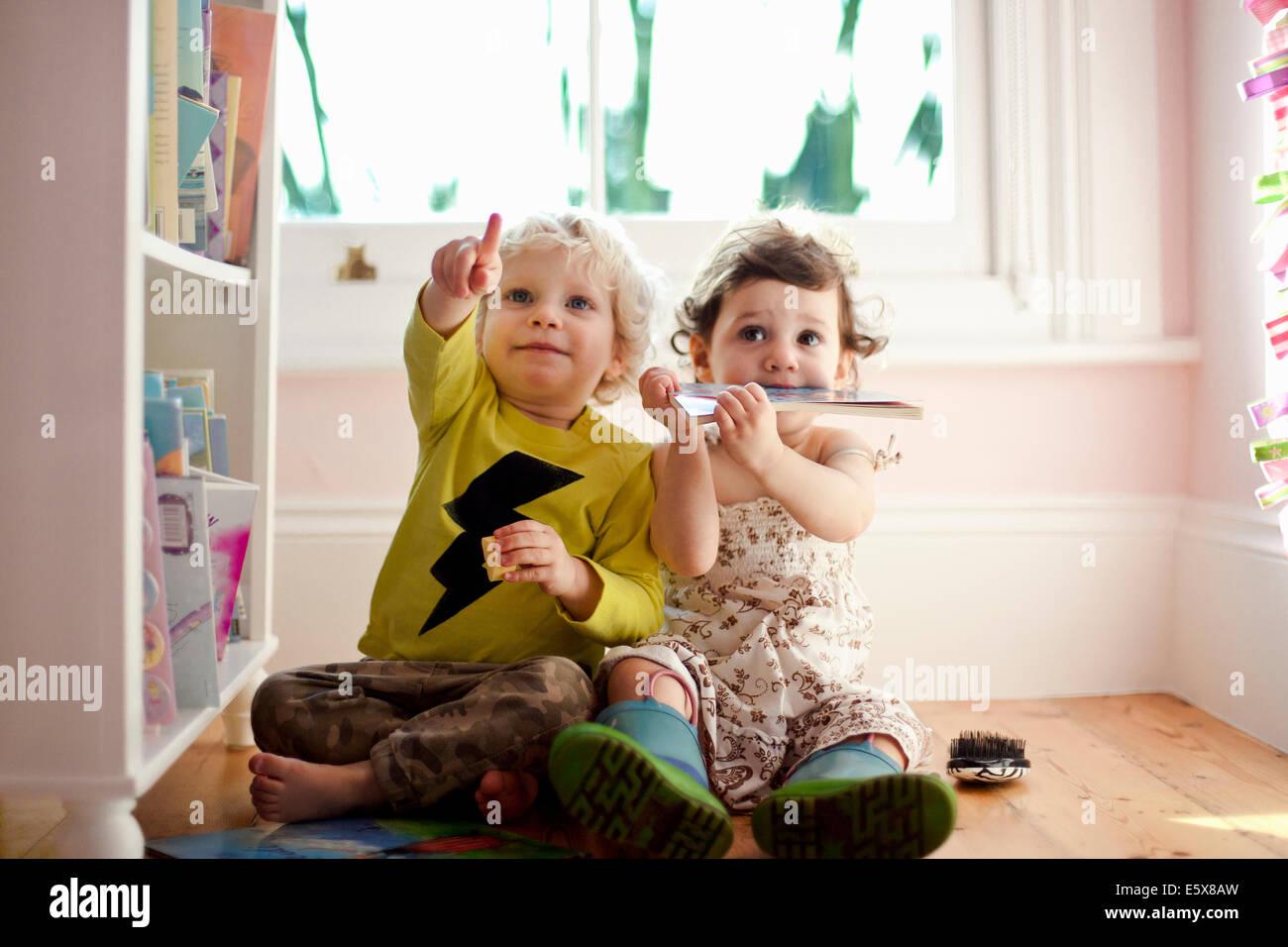 Macho y hembra toddler amigos apuntando y mirando hacia arriba Foto de stock