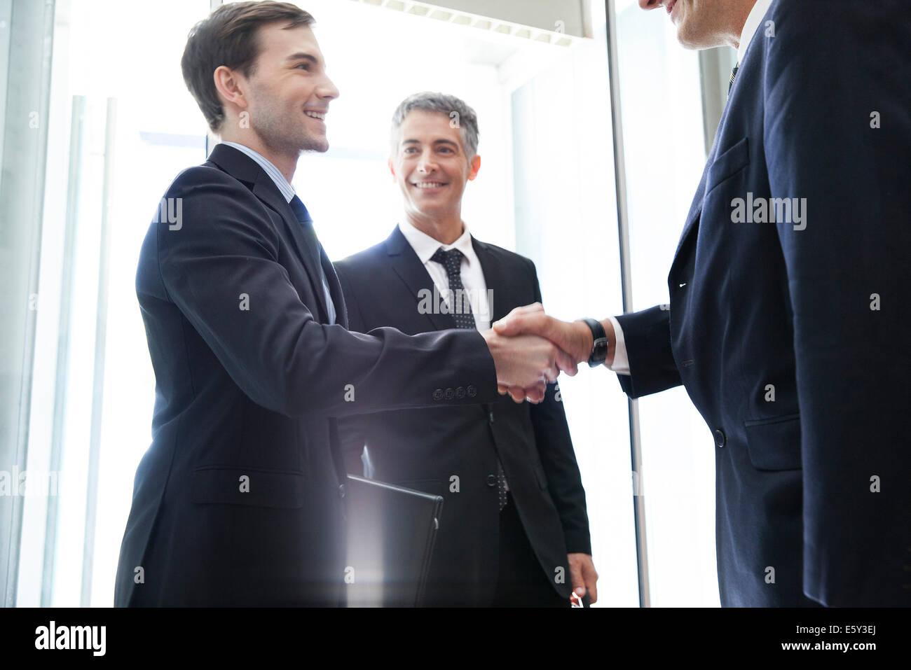 Un apretón de manos con el joven empresario Senior Associate Foto de stock