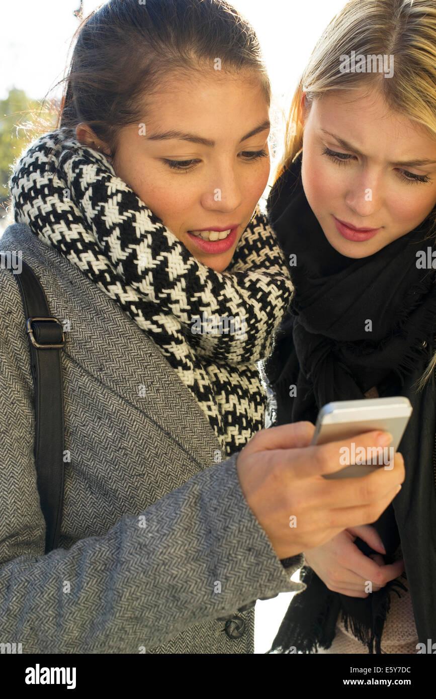 Las mujeres jóvenes en el exterior mirando juntos teléfono celular Foto de stock