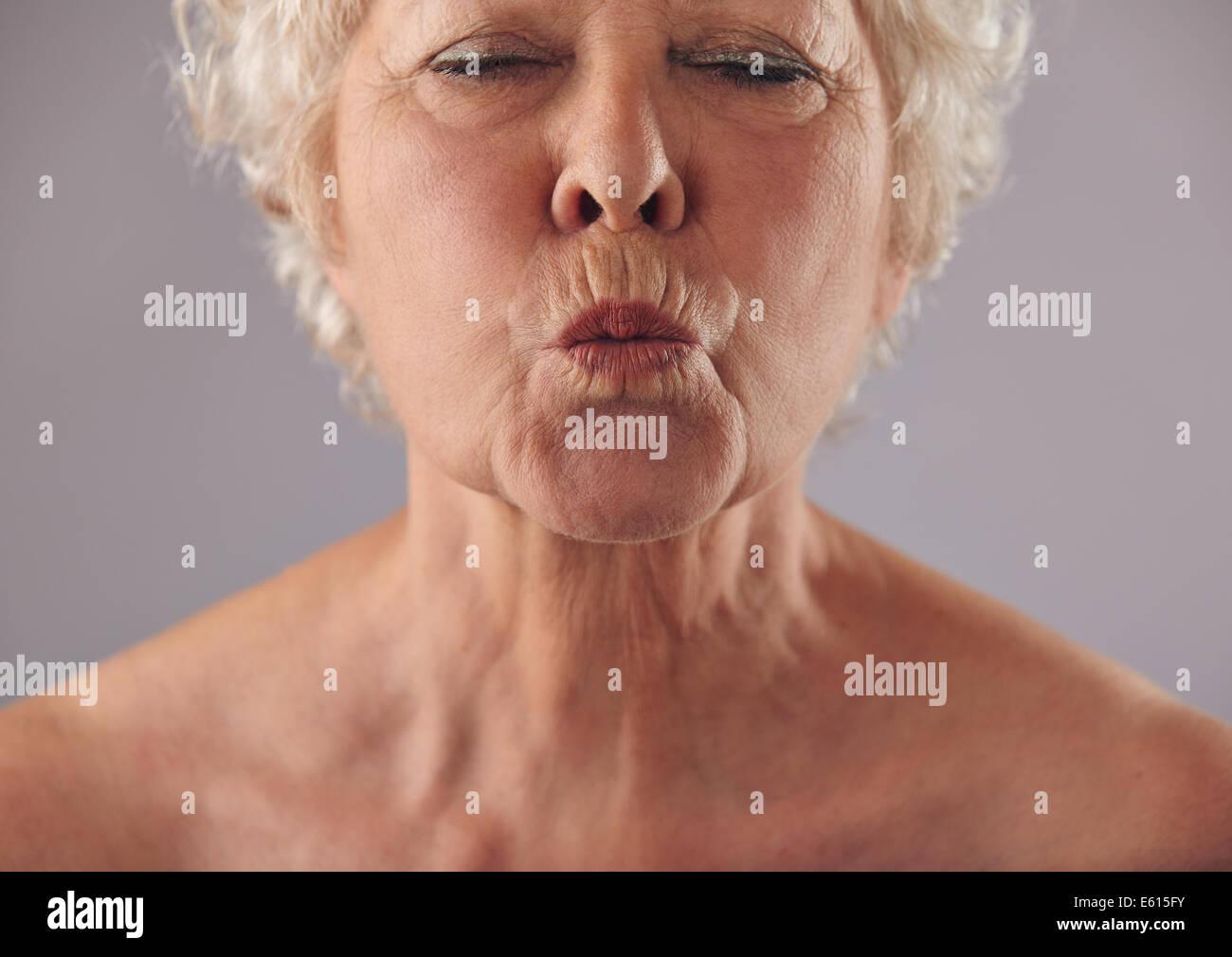Recorta el retrato de mujer mayor fruncir los labios. Hembra madura gesticulaciones contra un fondo gris Imagen De Stock