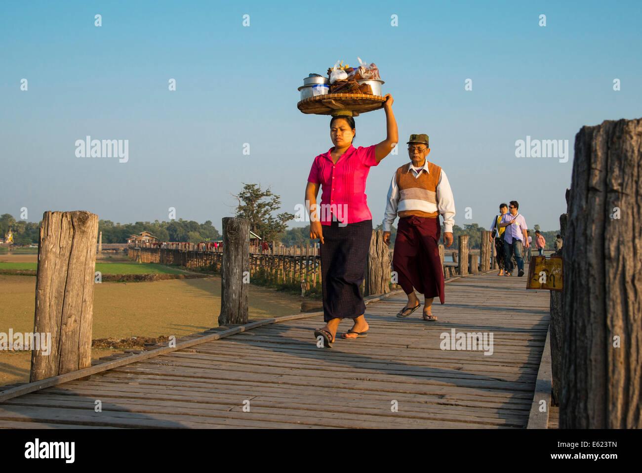Mujer con tanaka en su cara llevar comida en su cabeza en un puente de teca, U Bein Puente sobre el lago, Amarapura Thaungthaman Foto de stock