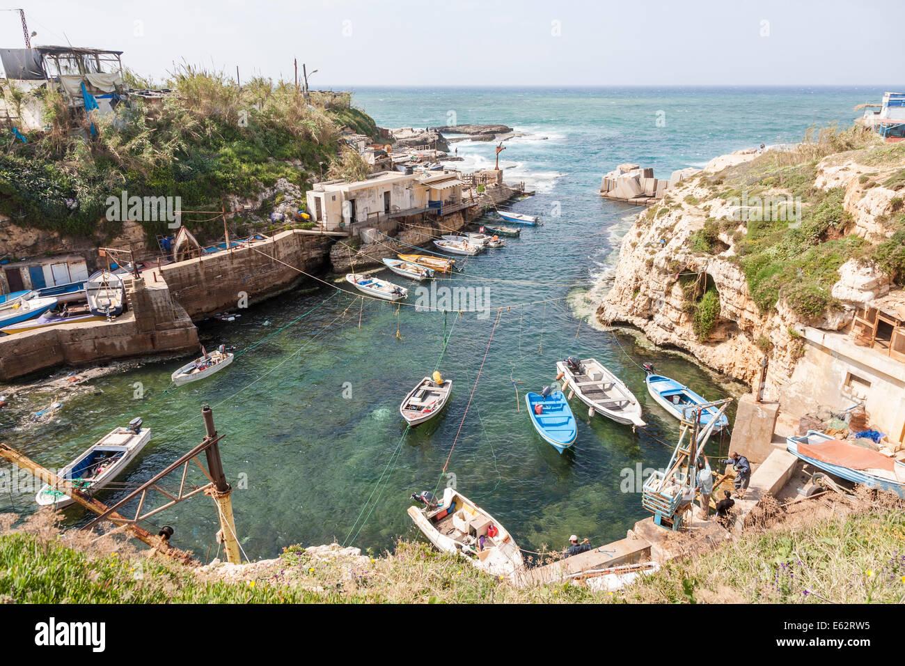La comunidad de la aldea pequeña de la pesca y del puerto en la costa mediterránea, con barcos amarrados Imagen De Stock