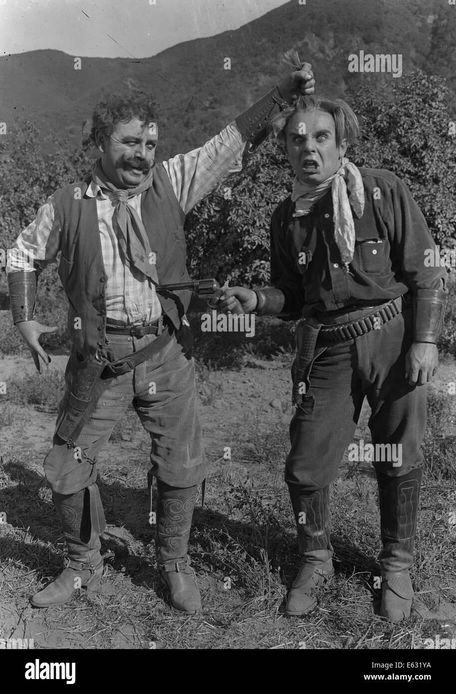 1910s dos vaqueros GOOFY una pistola apuntando al vientre de la otra tirando de su cabello todavía Película muda Foto de stock