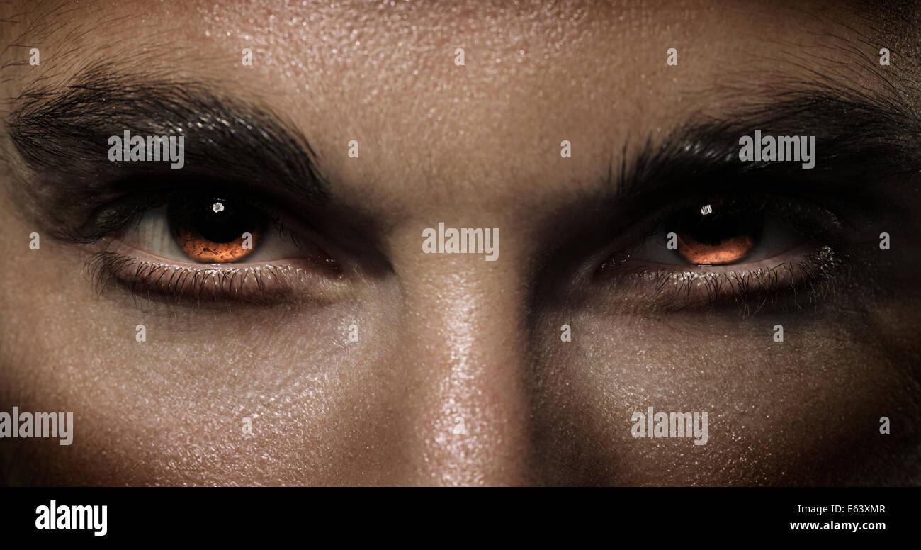 Closeup dramática del hombre feroz en los ojos ardor con rojo Imagen De Stock