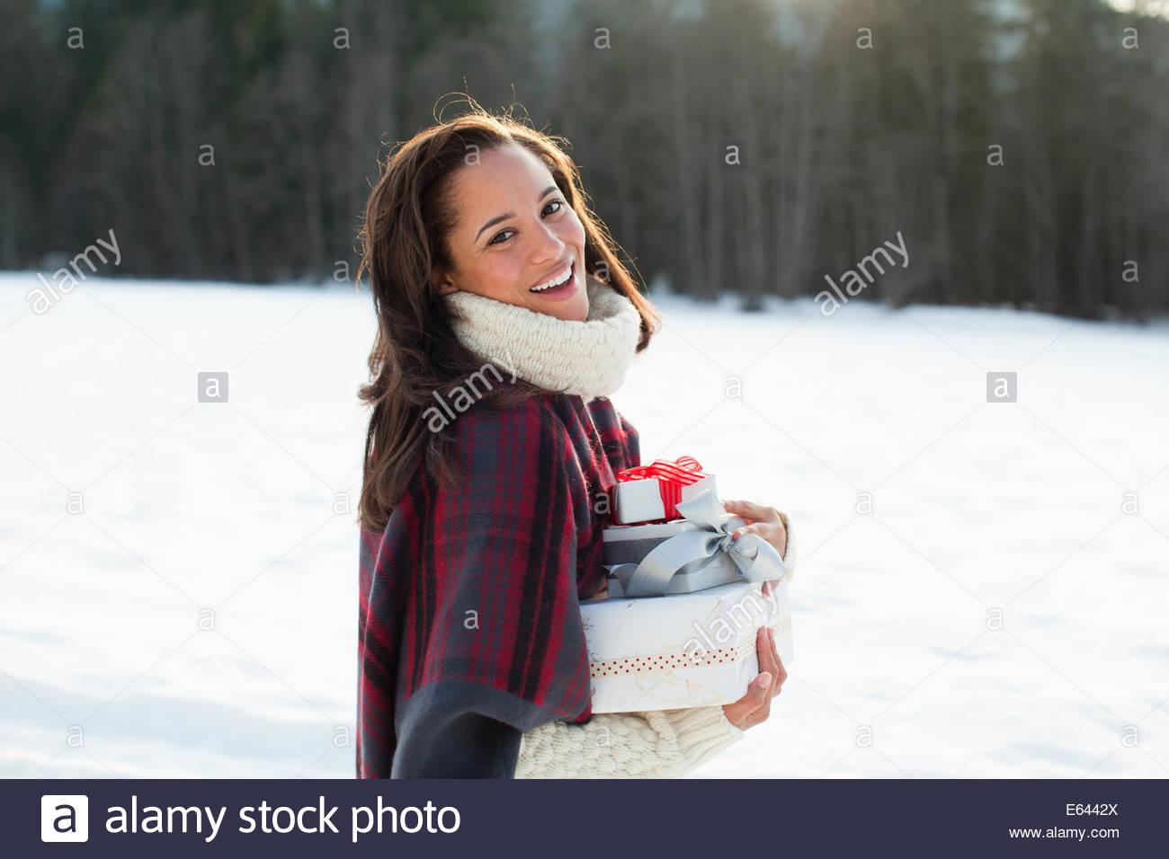 Retrato de mujer sonriente sosteniendo los regalos de Navidad en la nieve Imagen De Stock