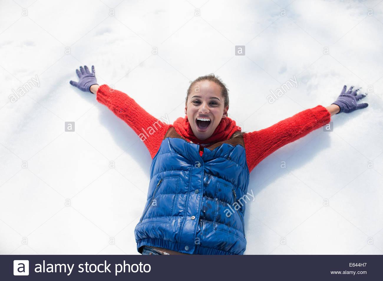 Mujer sonriente haciendo ángeles de nieve Imagen De Stock