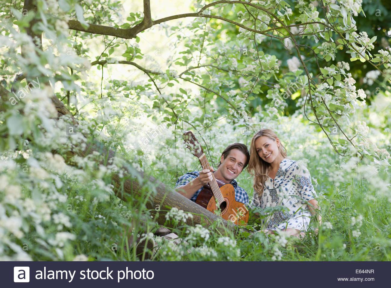 El hombre tocando la guitarra para novia en el bosque Imagen De Stock