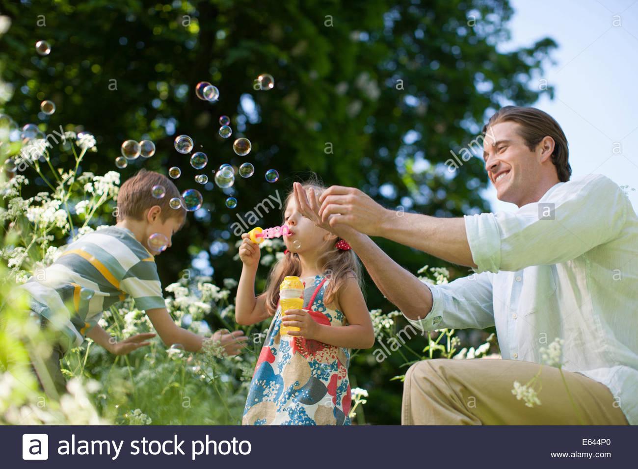 Familia jugando con burbujas en el exterior Imagen De Stock