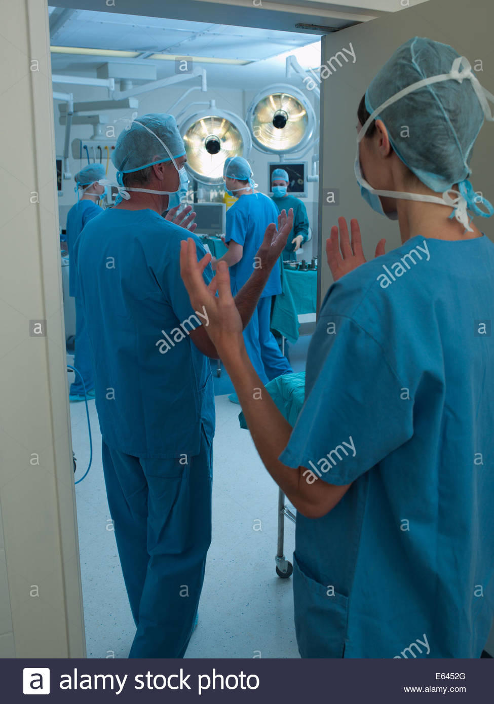 Los cirujanos con las manos limpias, entrando en quirófano Imagen De Stock