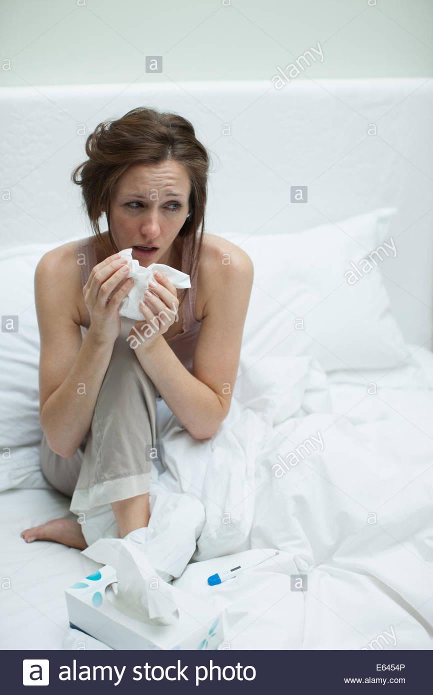 Mujer enferma en la cama sonarse la nariz Imagen De Stock