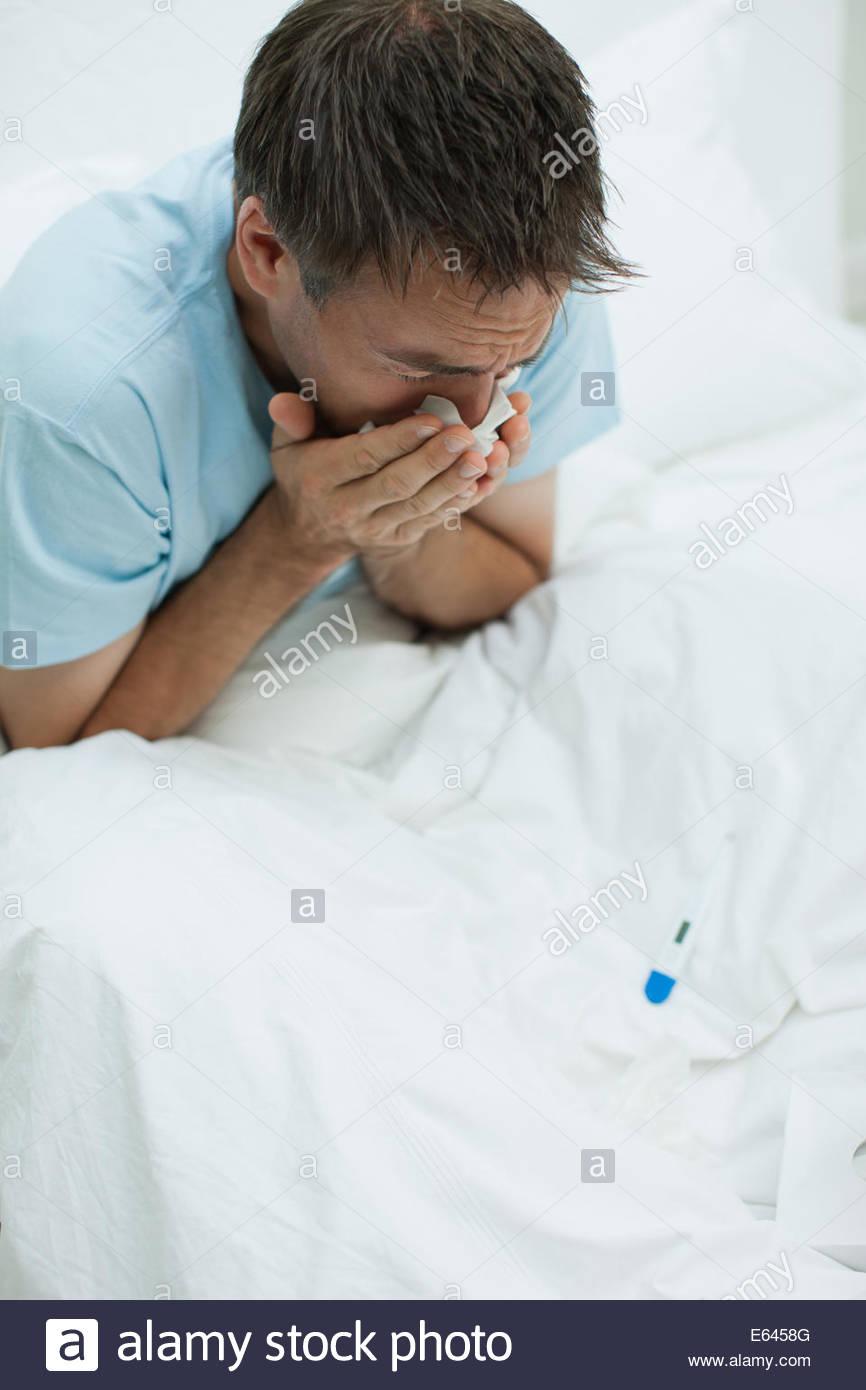 Hombre enfermo en la cama sonarse la nariz Imagen De Stock
