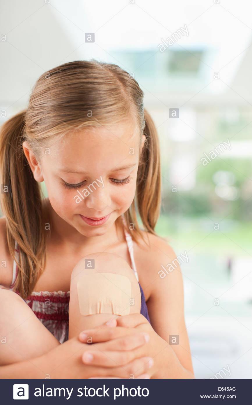 Chica sonriente con vendaje en la rodilla Imagen De Stock