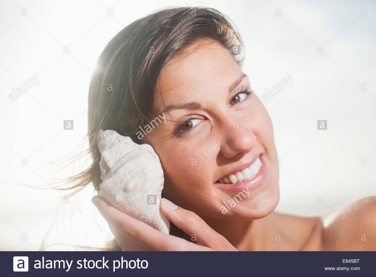 Cerca de la mujer escuchando seashell Imagen De Stock