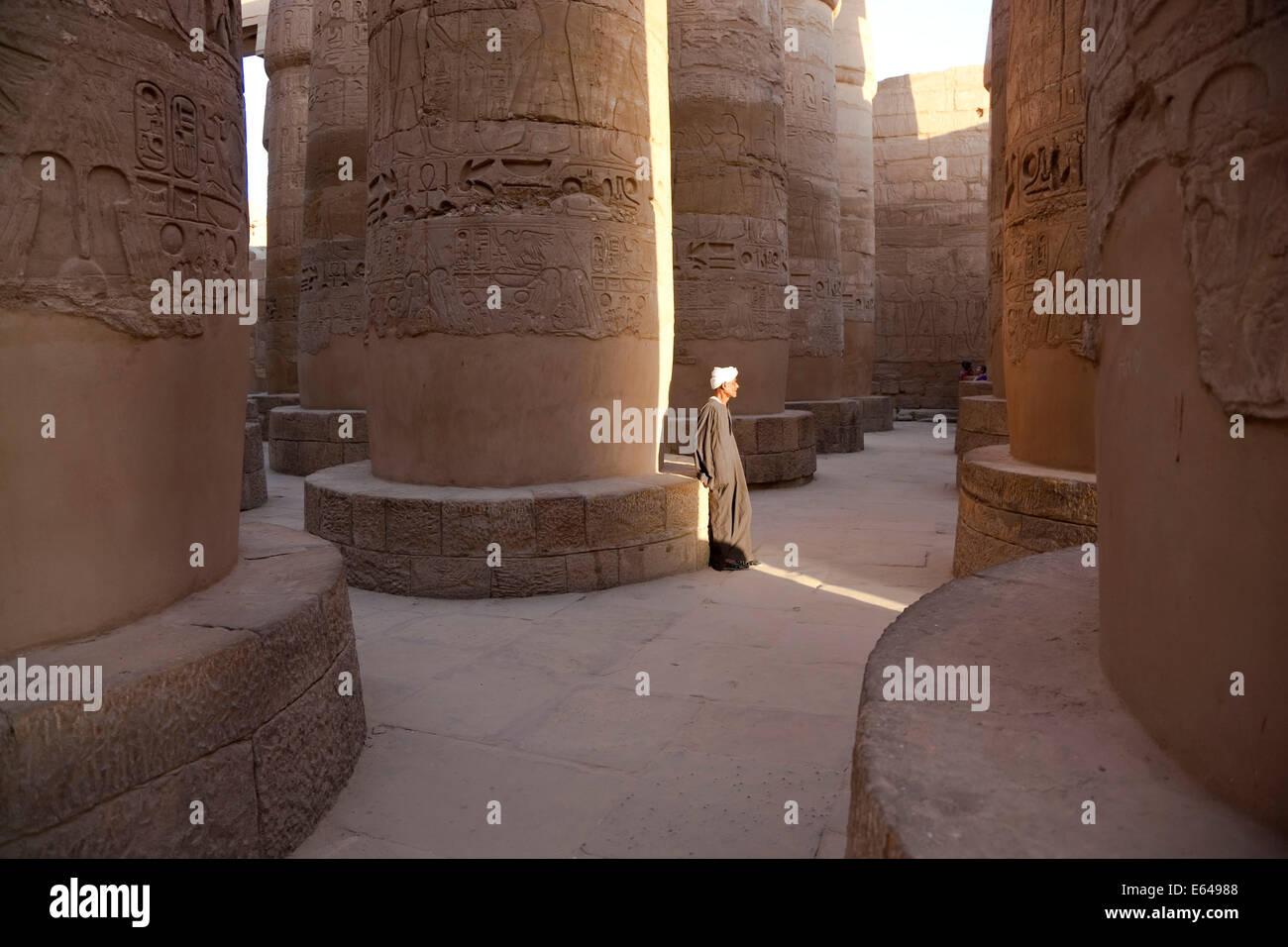 Egipto, Luxor y Karnak, el Gran Templo de Amón, gran sala hipóstila salen. Hombre con traje tradicional. Imagen De Stock