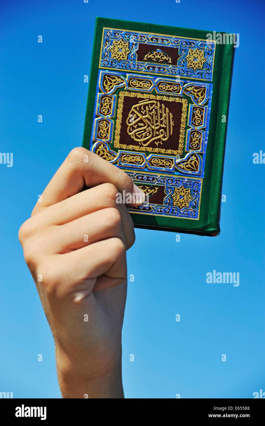 Mano sujetando el Corán Corán Santo libro Imagen De Stock