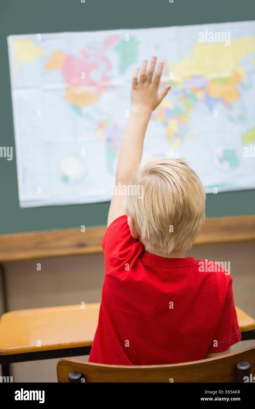Cute alumno levantando la mano en su escritorio en el aula Imagen De Stock