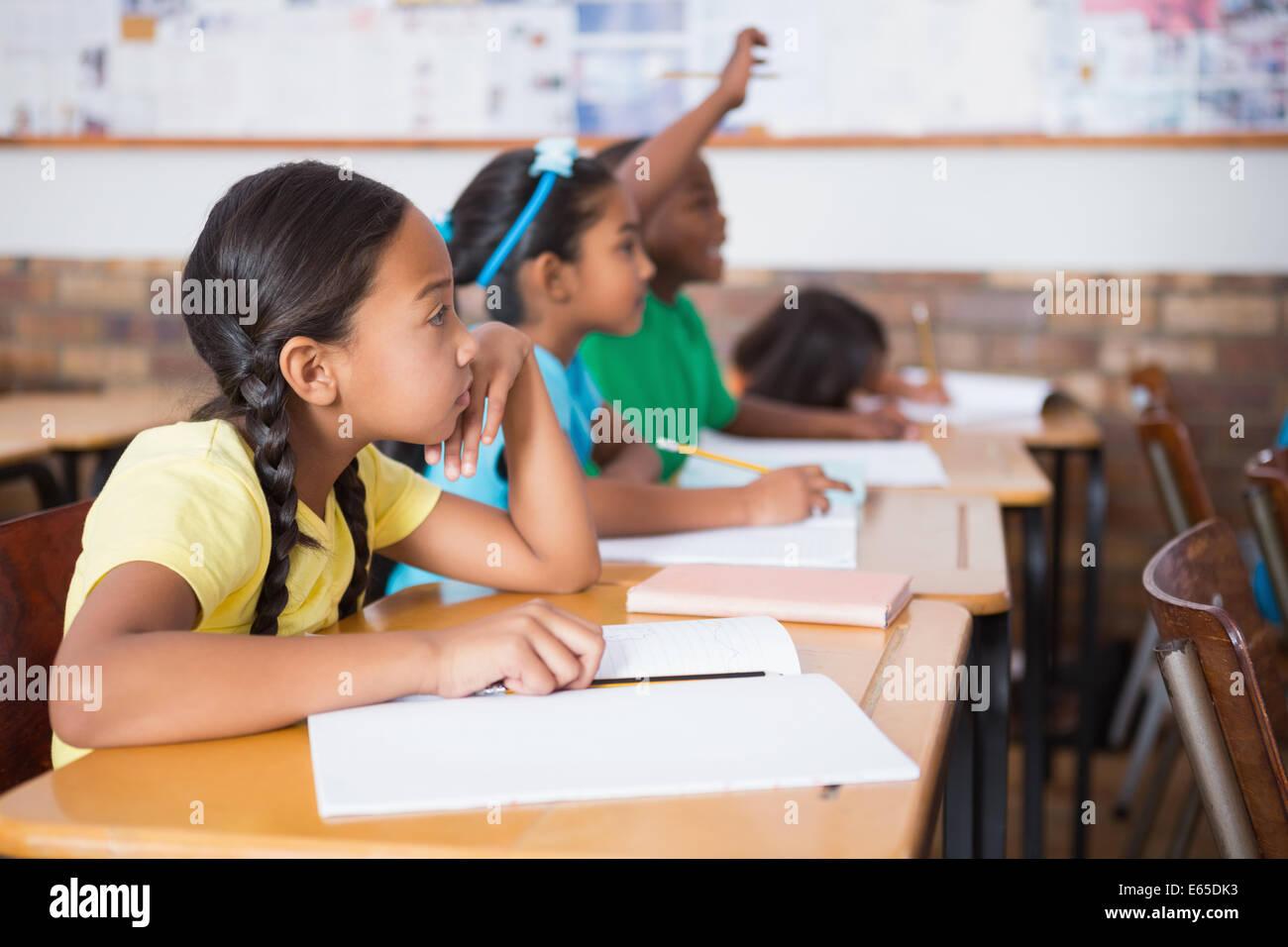 Cute alumno levantando la mano en el aula Imagen De Stock