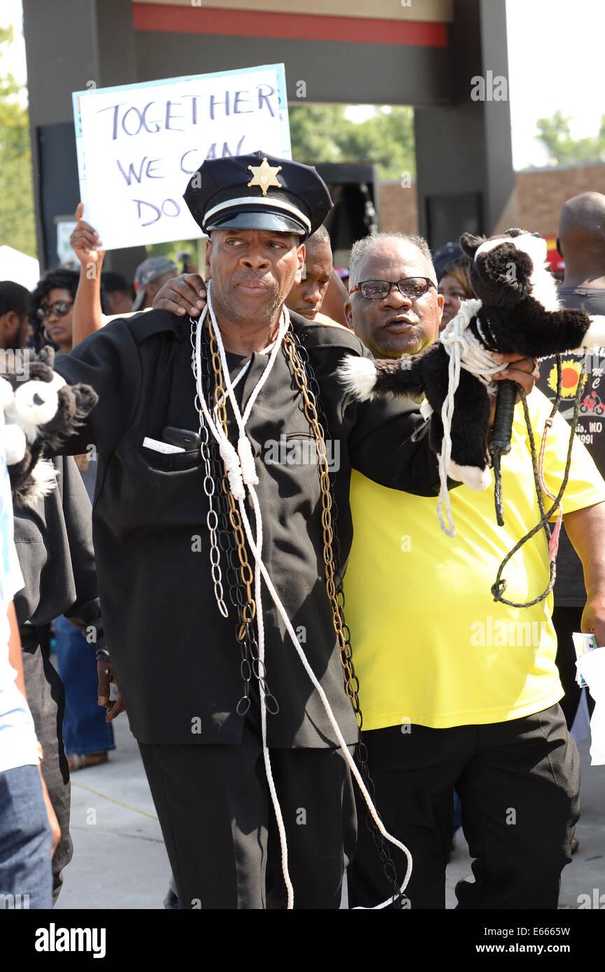 Ferguson, MO, Estados Unidos. El 15 de agosto de 2014. Los manifestantes reaccionan en el sitio de la destruida viaje rápido después de que el jefe de la policía de Jackson Thomas versión del nombre del funcionario que disparó Michael Brown. Foto de stock