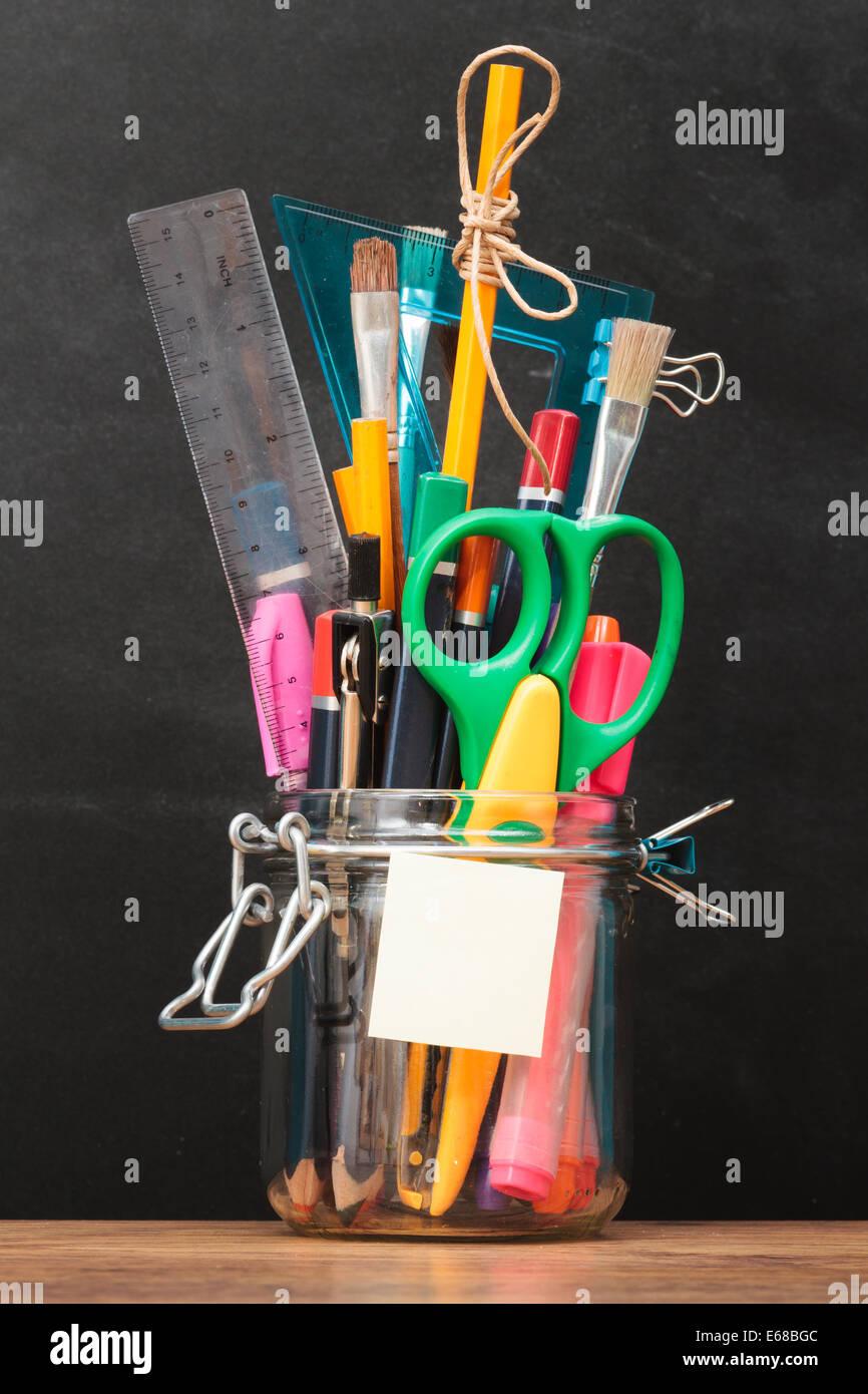 Accesorios escolares en tarro en escritorio con pizarra en el fondo Imagen De Stock