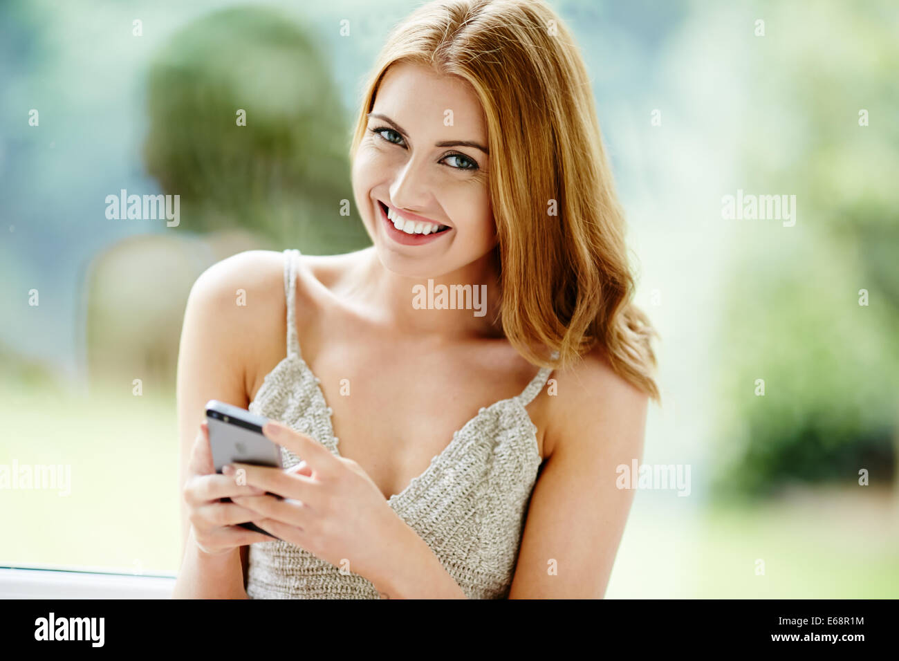 Pretty girl a través de teléfono móvil Imagen De Stock