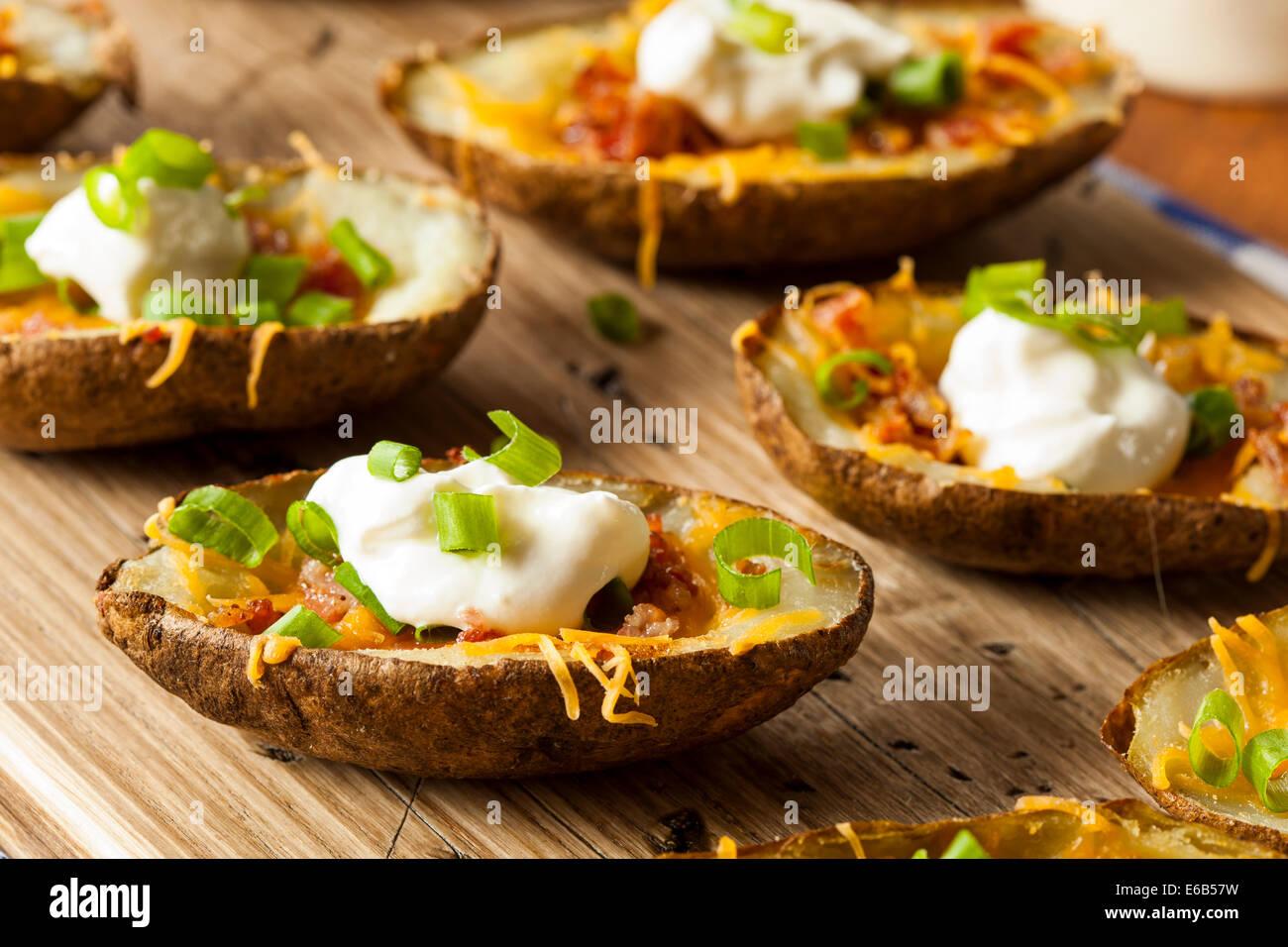 Las pieles de patata casero con tocino y queso crema agria Imagen De Stock