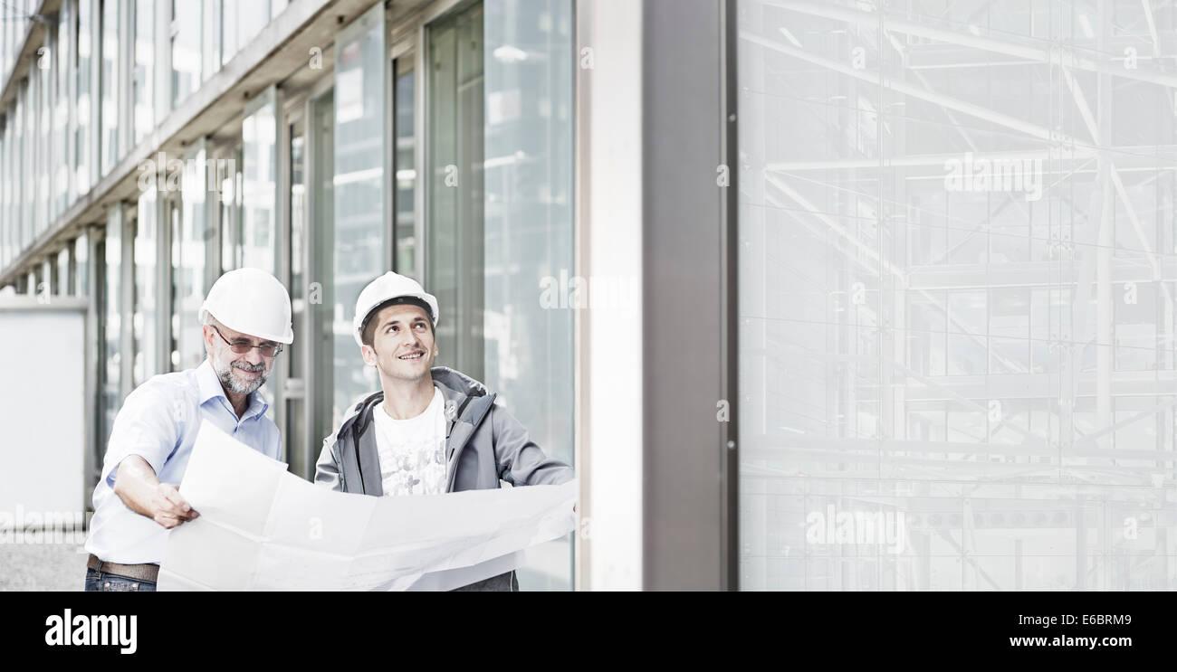 Dos ingenieros, 55-65 y 25-35 años de edad, portando cascos, de pie delante de un edificio y mirando un plano Imagen De Stock
