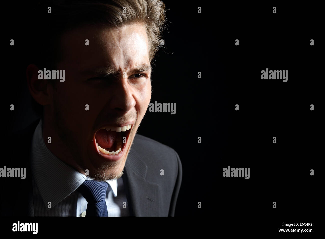 Empresario enojado gritos aislados en un fondo negro Foto de stock