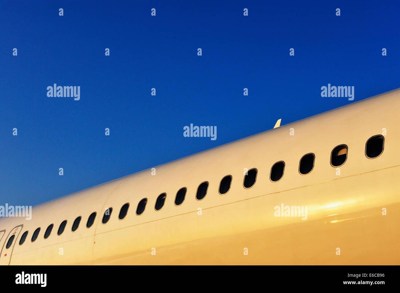 El fuselaje del avión con la hilera de ventanas de ojo de buey al amanecer. Imagen De Stock