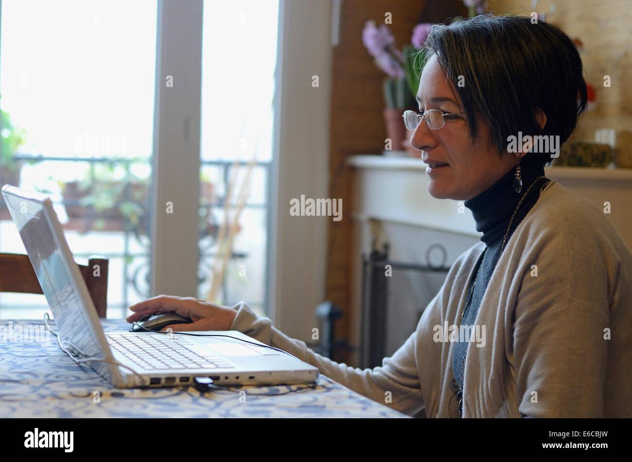 Mujer de mediana edad utilizando un equipo portátil en casa Imagen De Stock