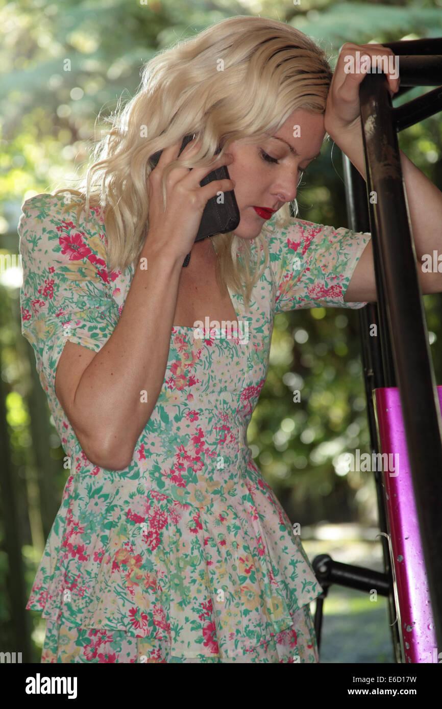 Mujer al teléfono discutiendo sus problemas de autos de carrera en miniatura Imagen De Stock