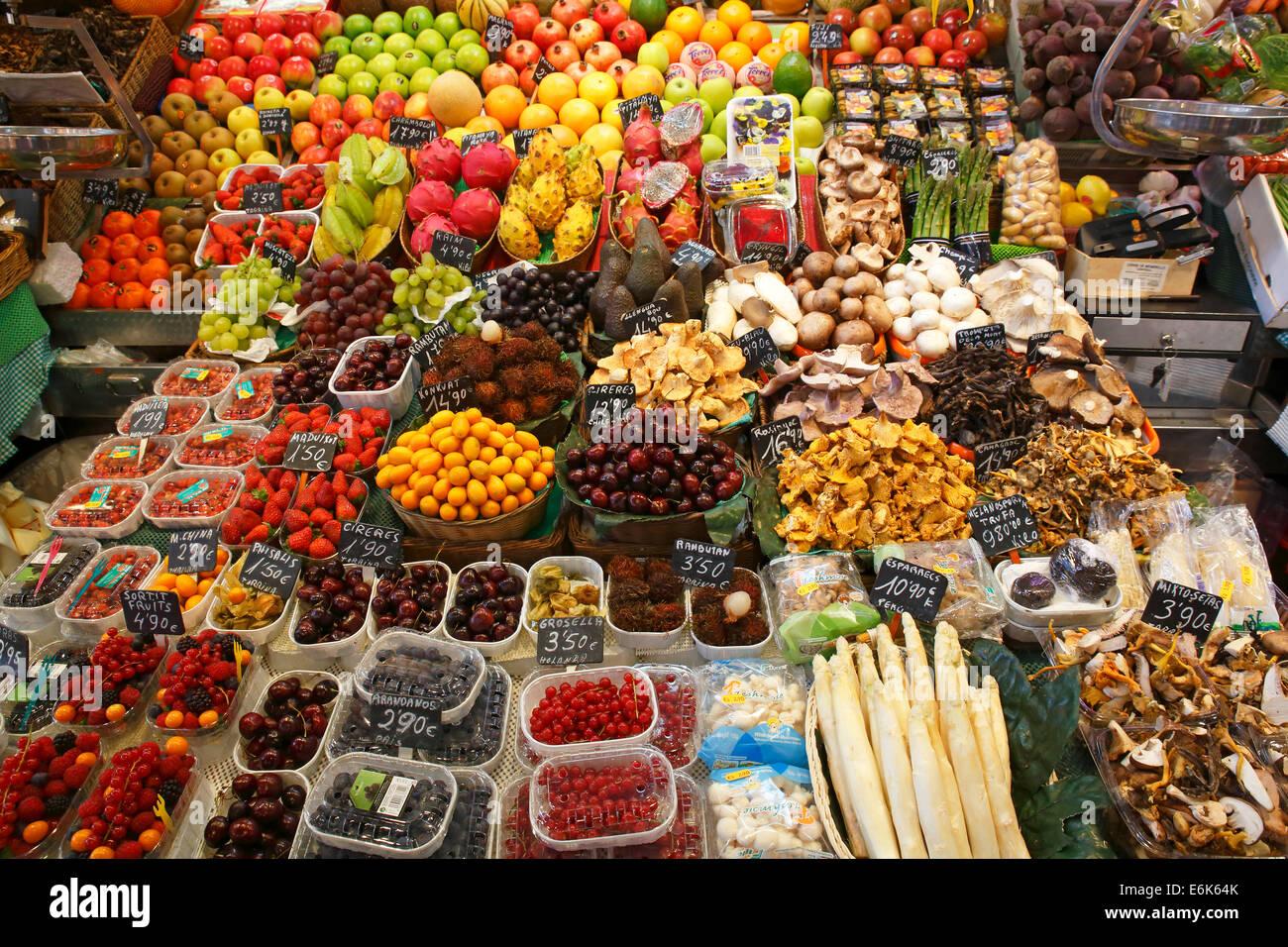 Puesto en el mercado vendiendo frutas exóticas, frutas, setas y verduras, antiguo mercado halls, el Mercat de la Foto de stock