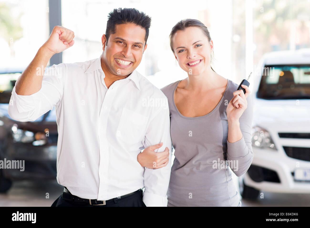Emocionada joven pareja acaba de comprar un nuevo coche de concesionario Imagen De Stock