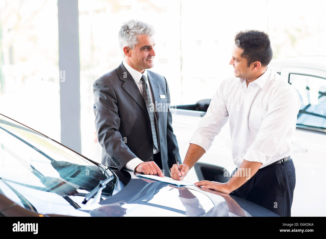 Senior vendedor de coches acaba de realizar una venta a clientes jóvenes Imagen De Stock