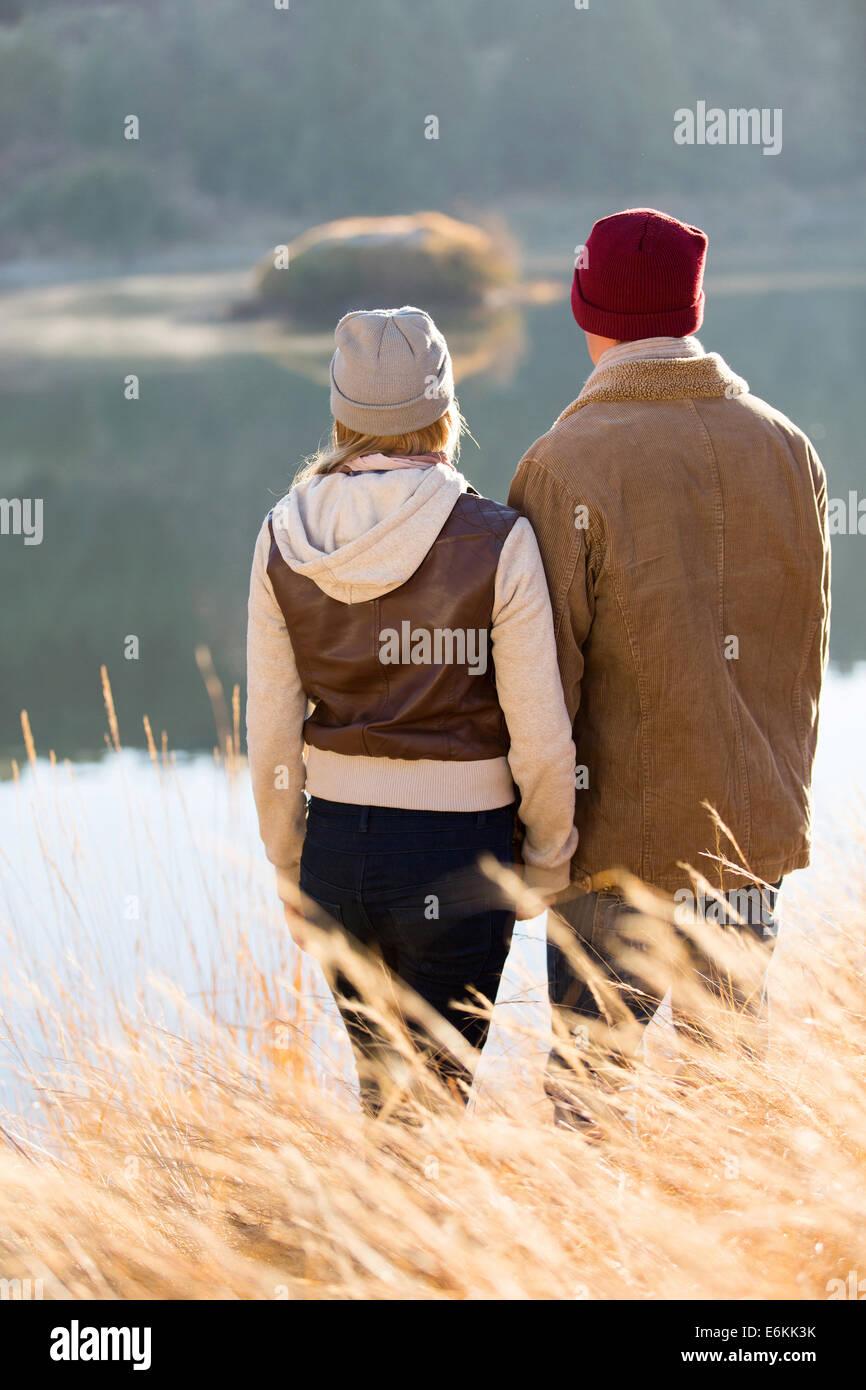 Pareja joven de pie en el lago del parque en otoño Imagen De Stock