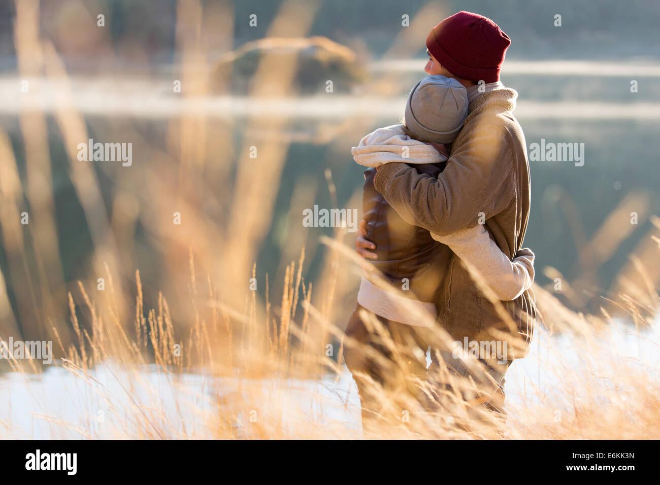 Vista posterior de la entrañable pareja joven abrazando en invierno Imagen De Stock
