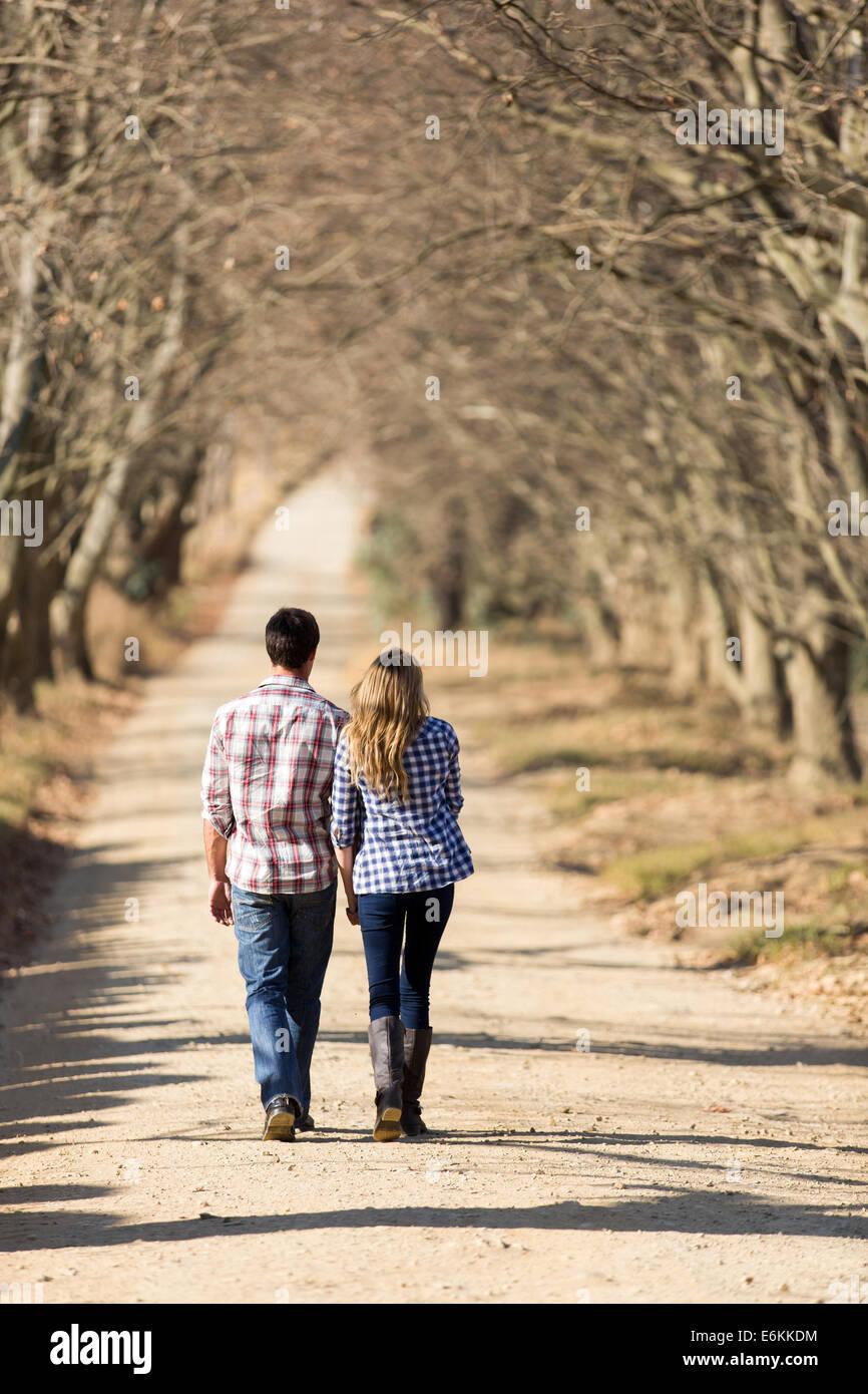 Vista posterior de la entrañable pareja joven caminando en el país por carretera en otoño Imagen De Stock