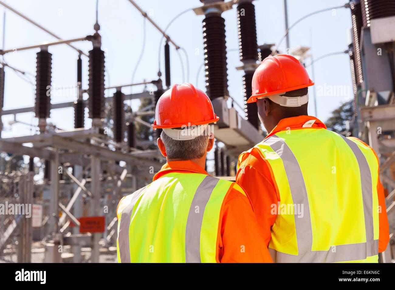Vista posterior de dos ingenieros eléctricos en la subestación Imagen De Stock