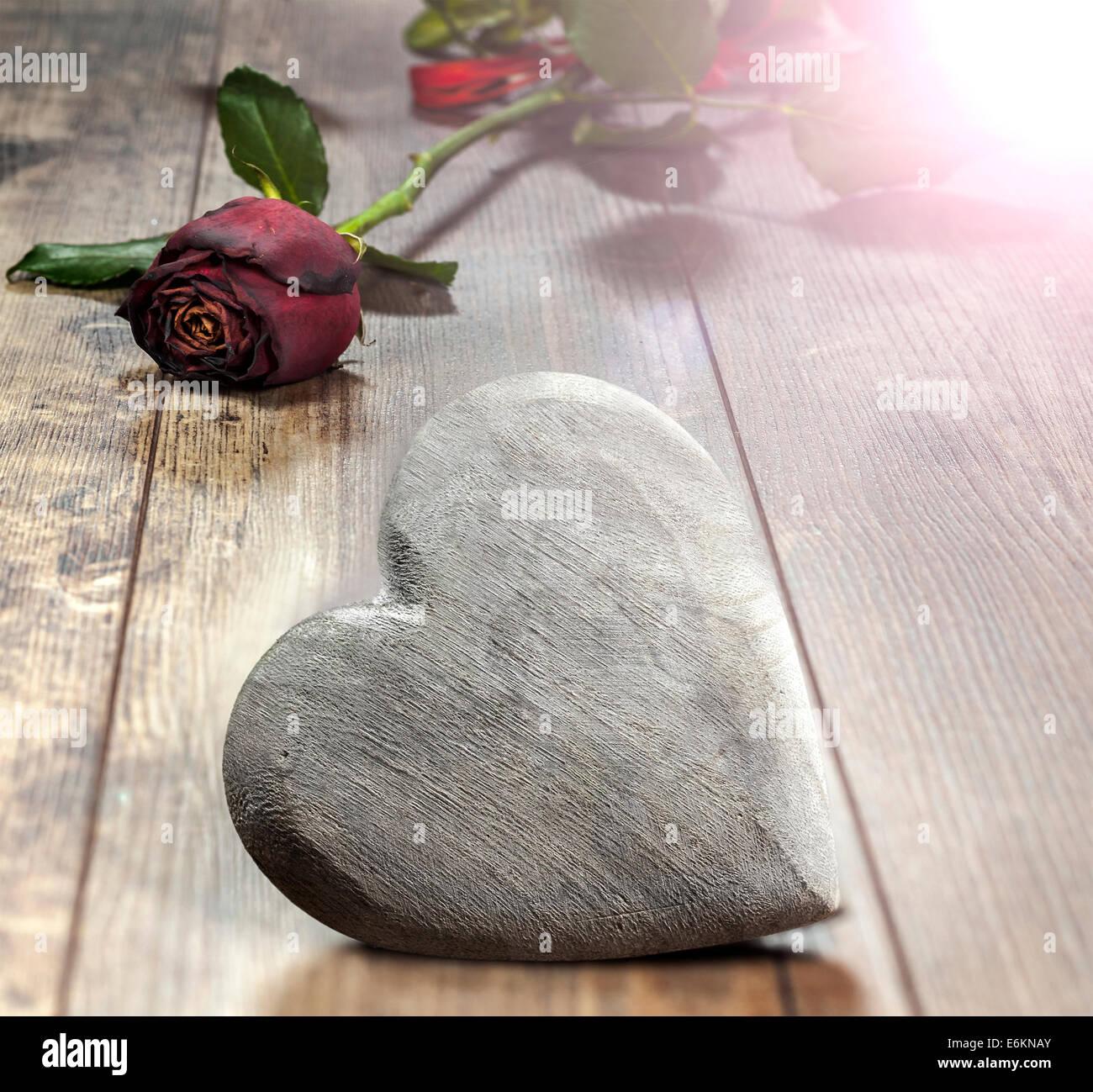 Símbolo del día de San Valentín. Corazón sobre un fondo de madera con rosa roja. Imagen De Stock