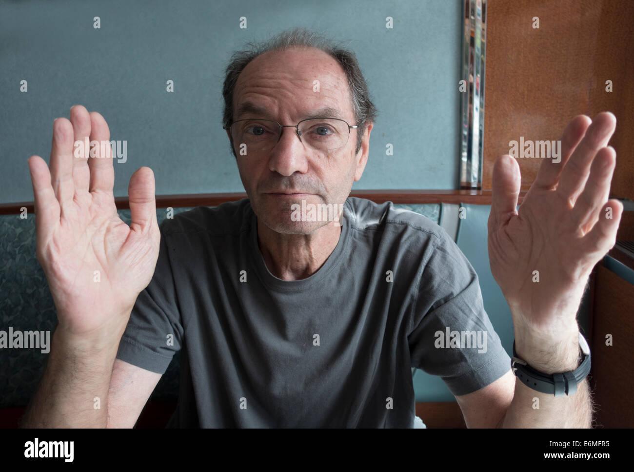 Hombre sentado a la mesa, gesticulando con las manos para hacer un punto Imagen De Stock